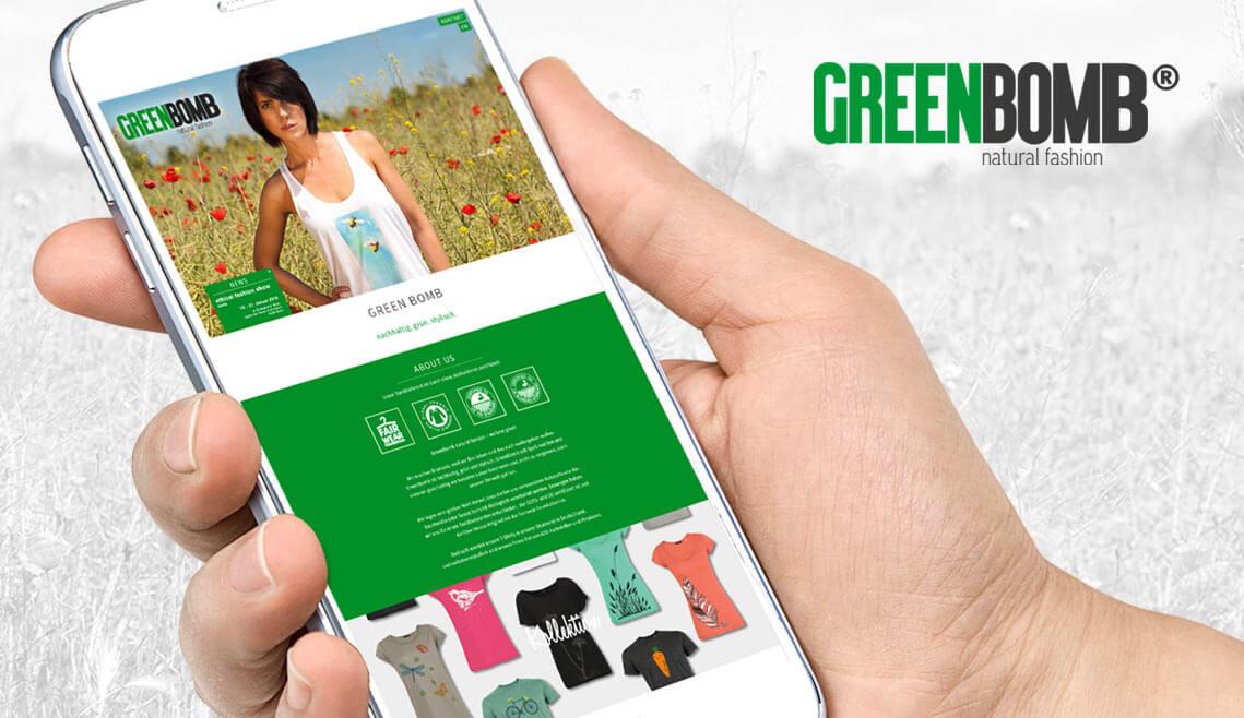 Webdesign aus Essen von mediadesign linke - Ansicht eines Smartphones und menschliche Hand mit www.greenbomb.de auf dem Display, Ansicht Website Greenbomb